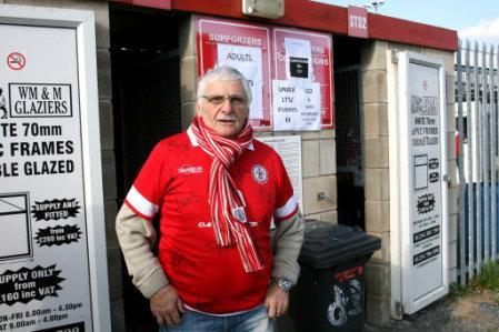 An Accrington Stanley fan stands outside the turnstiles at The Crown Ground
