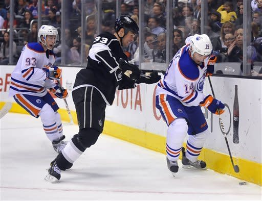 Edmonton Oilers right winger Jordan Eberle right, controls the puck as Los Angeles Kings defenseman Willie Mitchell, center, defends during the first period of an NHL hockey game, Monday, April 2, 2012, in Los Angeles. Oilers' Ryan Nugent-Hopkins is at left. (AP Photo/Richard Hartog)