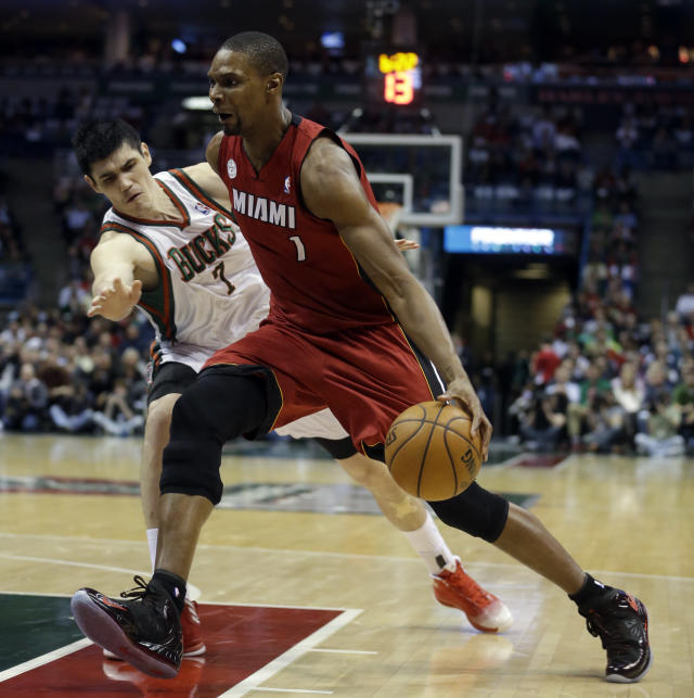 Miami Heat's Chris Bosh, right, drives past Milwaukee Bucks' Ersan Ilyasova during the first half of Game 3 in their first-round NBA basketball playoff series on Thursday, April 25, 2013, in Milwaukee. (AP Photo/Morry Gash)