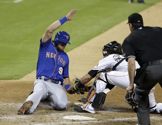 New York Mets' Kirk Nieuwenhuis (9) is tagged out at home plate by Miami Marlins catcher Jarrod Saltalamacchia, center, as Nieuwenhuis tried to score on a fly ball hit by Chris Young in the ninth inning of a baseball game as home plate umpire Lance Barrett, right, watches the play in Miami, Friday, June 20, 2014. The Marlins won 3-2. (AP Photo/Alan Diaz)