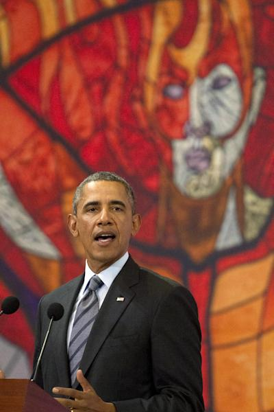 "President Barack Obama speaks in front of a printed version of a stained glass window from the Cosmovitral, at a news conference at state government palace in Toluca, Mexico, Wednesday, Feb. 19, 2014, after the seventh trilateral North American Leaders Summit Meeting. This year's theme is ""North American Competitiveness."" (AP Photo/Jacquelyn Martin)"