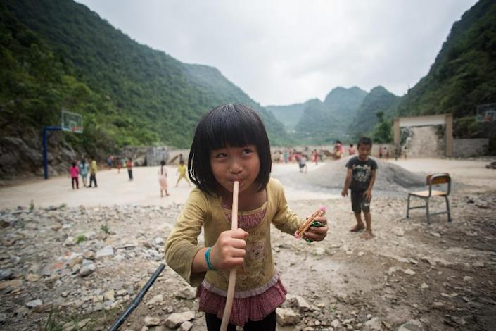 A schoolgirl drinks rain water from a hose in the schoolyard of the Chongshan Primary School in Longfu Township, in China's Guangxi province, on June 19, 2015 (AFP Photo/Johannes Eisele)