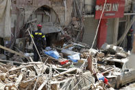 """A French fireman and a rescue dog search in the rubble of a building after the Tuesday explosion at the seaport of Beirut, in Beirut, Lebanon, Thursday, Aug. 6, 2020. Lebanese officials targeted in the investigation of the massive blast that tore through Beirut sought to shift blame for the presence of explosives at the city's port, and the visiting French president warned that without serious reforms the country would """"continue to sink."""" (AP Photo/Hassan Ammar)"""