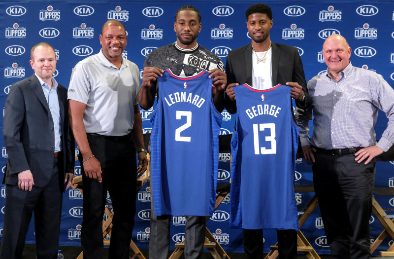 FILE - In this July 24, 2019, file photo, players Kawhi Leonard, center, and Paul George, second from right, hold their new team jerseys as they pose with Clippers president of basketball operations Lawrence Frank, left, head coach Doc Rivers, second from left, and team chairman Steve Ballmer, right, during a news conference in Los Angeles. The NBA's balance of power has shifted to the Clippers, who have never advanced beyond the second round let alone won a championship. All that is expected to change behind Leonard and George, both regarded as two of the best two-way players in the league. (AP Photo/Ringo H.W. Chiu, File)