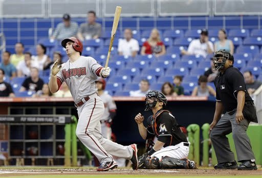 Arizona Diamondbacks' Paul Goldschmidt, left, watches after hitting a two-run home run as Miami Marlins catcher Rob Brantly, right, looks on in the first inning during a baseball game in Miami, Friday, May 17, 2013. At right is home plate umpire Adrian Johnson. (AP Photo/Lynne Sladky)