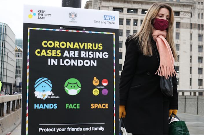 A woman walks past a coronavirus information sign on London Bridge, the morning after Prime Minister Boris Johnson set out further measures as part of a lockdown in England in a bid to halt the spread of coronavirus.