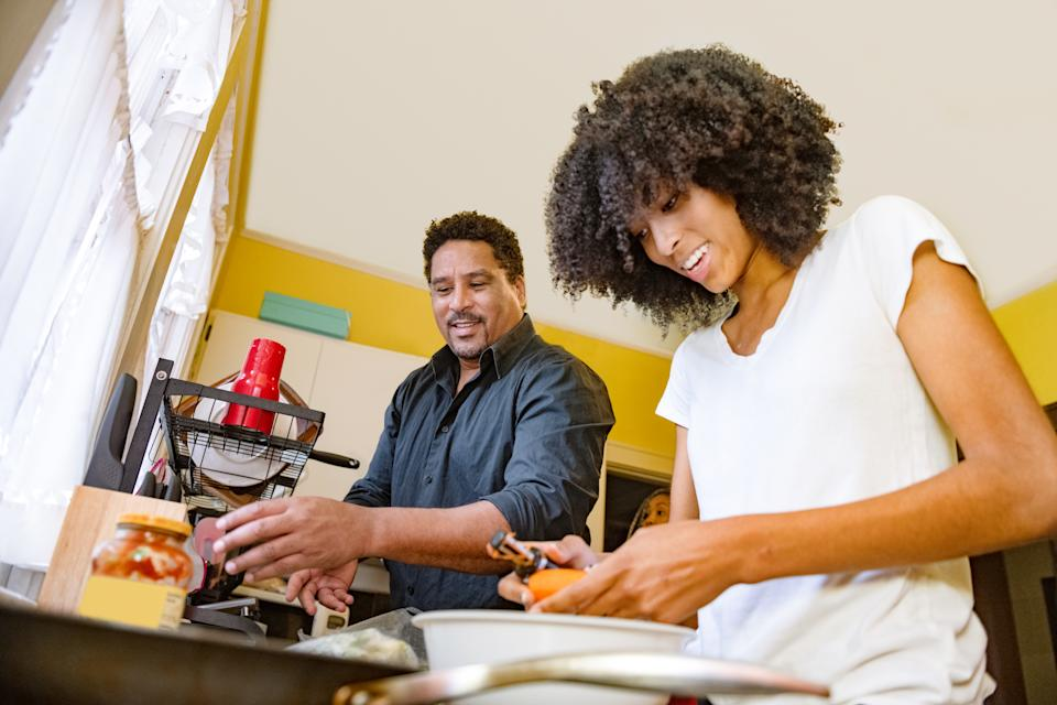 This is a wide angle photograph of an African American father in his 40s preparing food for cooking dinner with his 17 year old daughter in their home kitchen in Miami, Florida.