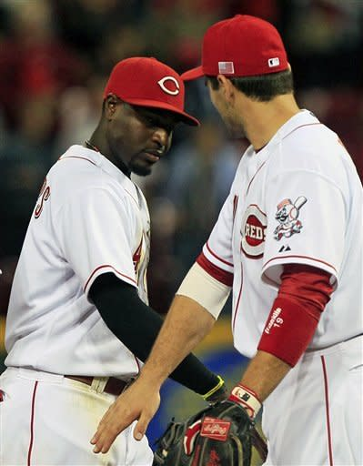 Cincinnati Reds' Brandon Phillips, left, and Joey Votto slap hands after they defeated the Pittsburgh Pirates 5-3 in a baseball game, Tuesday, Sept. 11, 2012, in Cincinnati. Phillips hit a home run and had two RBI's in the game. (AP Photo/Al Behrman)