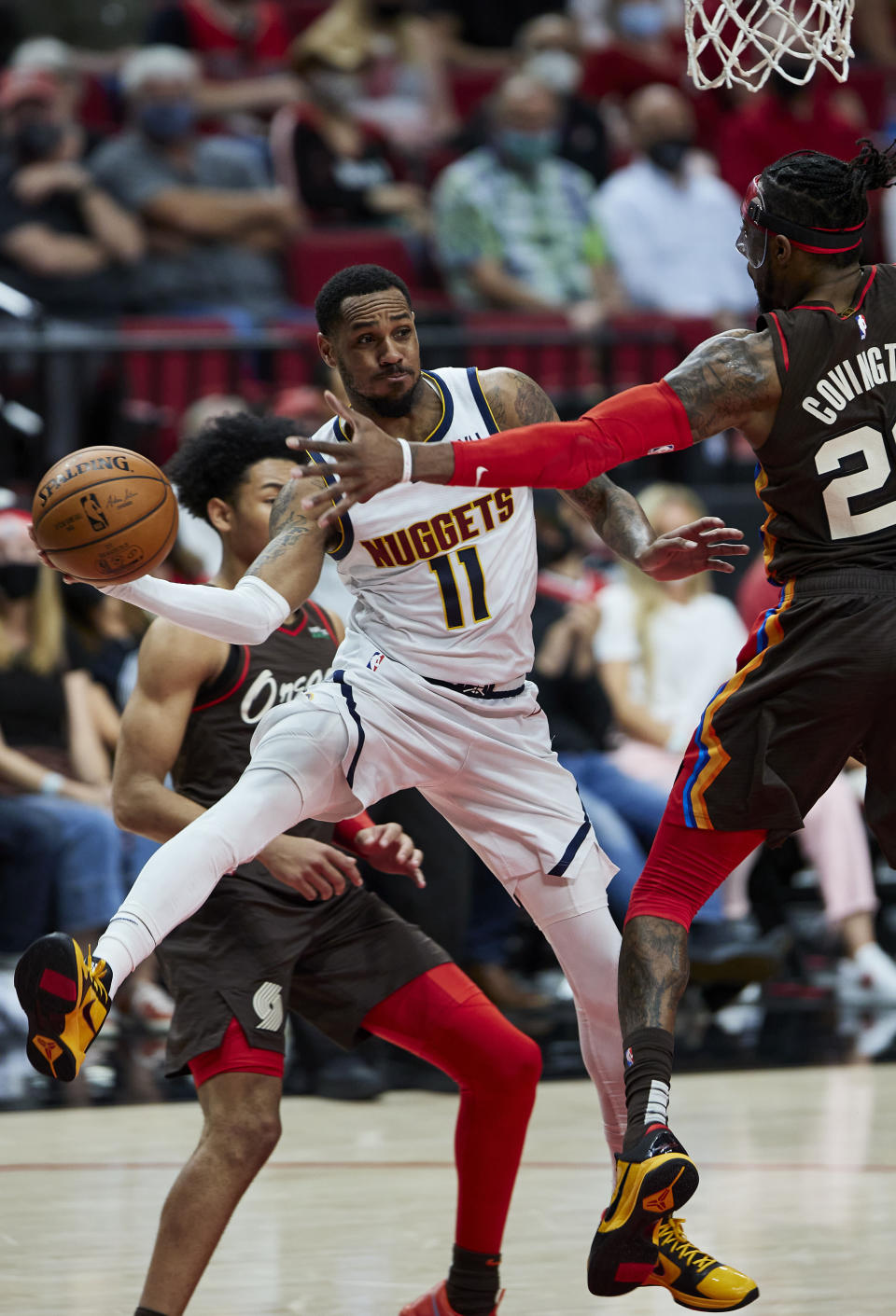 Denver Nuggets guard Monte Morris (11) passes the ball around Portland Trail Blazers forward Robert Covington, right, during the first half of Game 6 of an NBA basketball first-round playoff series Thursday, June 3, 2021, in Portland, Ore. (AP Photo/Craig Mitchelldyer)