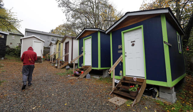 <p> In this photo taken Thursday, Nov. 9, 2017, a resident walks past a row of tiny houses at a homeless encampment in Seattle where full size homes stand behind. Tiny homes could be the solution to all kinds of housing needs, offering warmth and security for the homeless, an affordable option for expensive big cities and simplicity for people who want to declutter their lives. However, that seemingly broad support fails to translate into acceptance when tiny home developers try to build next door. (AP Photo/Elaine Thompson) </p>