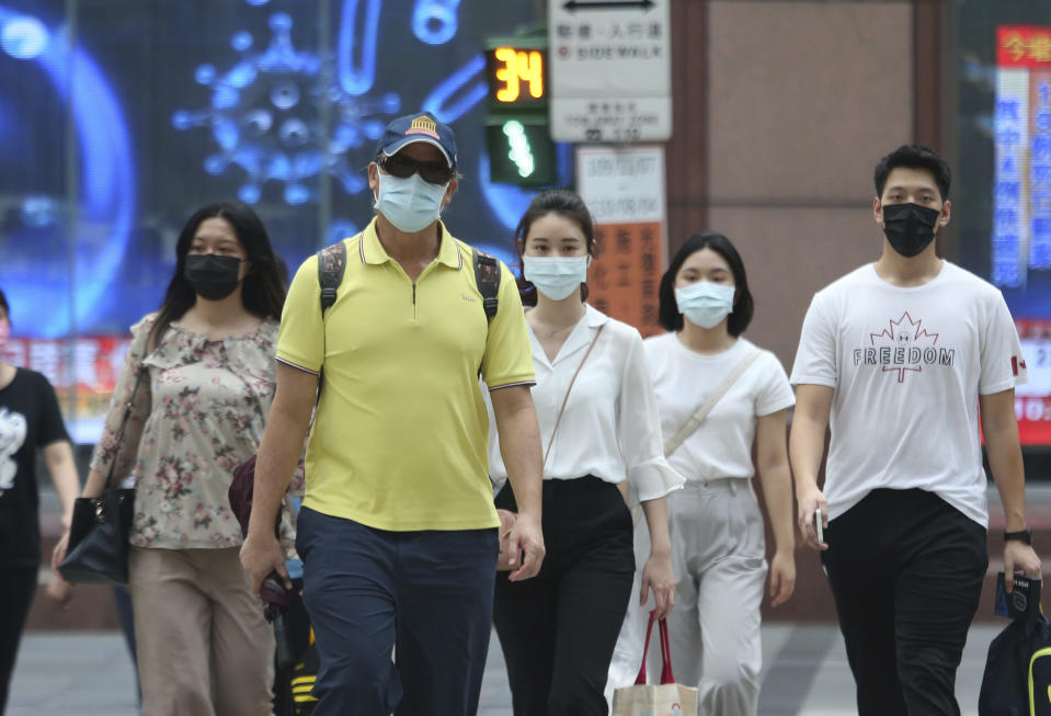 People wear face masks to help protect against the spread of the coronavirus after the COVID-19 alert rose to level 3 in Taipei, Taiwan, Monday, July 12, 2021. Two Taiwanese high-tech companies announced a donation Monday of 10 million doses of anti-coronavirus vaccine made by Germany's BioNTech to the island's government, which faces political obstacles in fighting the pandemic. (AP Photo/Chiang Ying-ying)