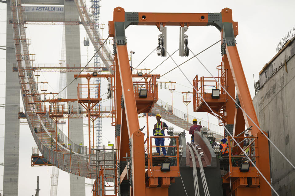 Workers install cables on the structure during a ceremony marking 100 years of diplomatic relations between Japan and Romania, at the construction site of a suspension bridge over the Danube river in Braila, Romania, Thursday, Aug. 26, 2021. The bridge, built by Japanese and Italian companies, with a span of 1,974.3 meters, will be the largest of its kind in Romania and the third in the European union.(AP Photo/Vadim Ghirda)
