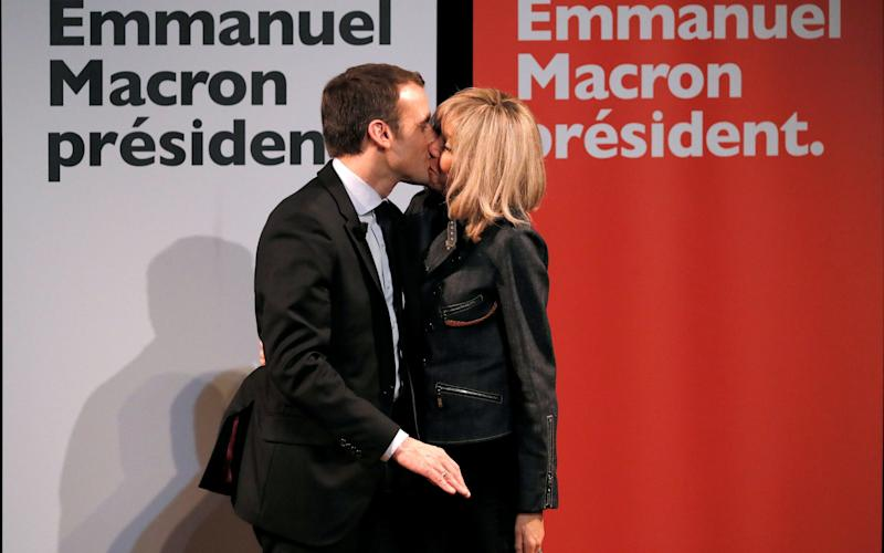 Emmanuel Macron kisses his wife Brigitte Trogneux, kiss as they attend a meeting for Women's Day in Paris - Credit:  GONZALO FUENTES/Reuters