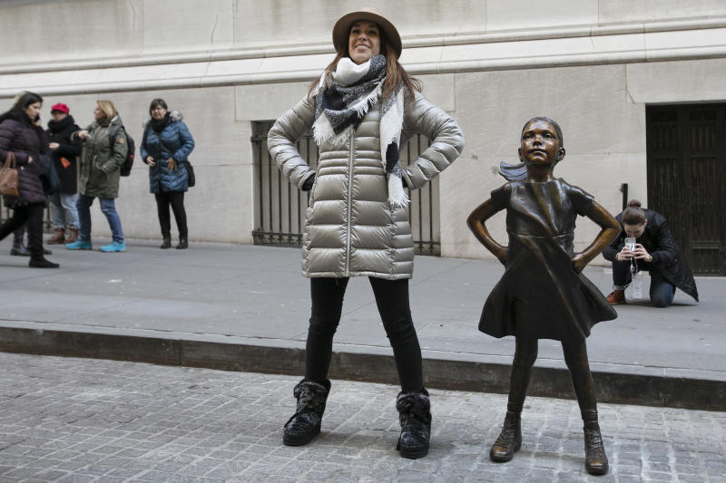 "A woman poses with the ""Fearless Girl"" statue after it is unveiled at its new location in front of the New York Stock Exchange, Monday, Dec. 10, 2018, in New York. The statue, considered by many to symbolize female empowerment, was previously located near the Charging Bull statue on lower Broadway. (AP Photo/Mark Lennihan)"