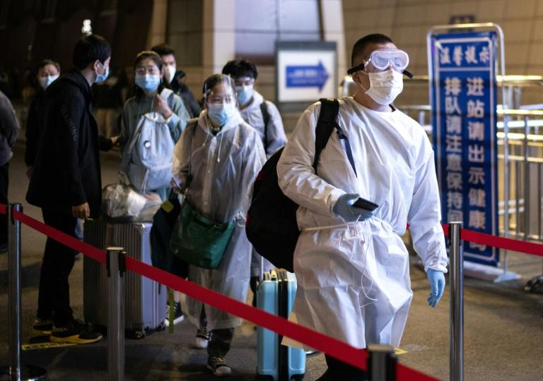Passengers wear hazmat suit as they arrive at the Wuhan Wuchang Railway Station in leave the original epicenter of the COVID-19 coronavirus (AFP Photo/NOEL CELIS)