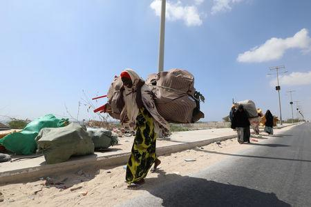 Women carry bags of plastic litter collected from a garbage dump to be recycled into roofing tiles at the Envirogreen recycling plant in Mogadishu, Somalia January 13, 2019. Picture taken January 13, 2019. REUTERS/Feisal Omar