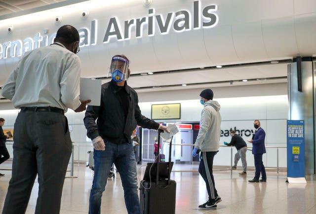 A masked passenger arrives at Heathrow in June