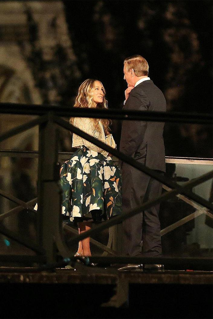 <p>Carrie and Big take their romance back to Paris in new photos from set. For the romantic outing, Sarah Jessica Parker is seen in an Oscar de la Renta floral print dress and a cropped metallic cardigan. </p>