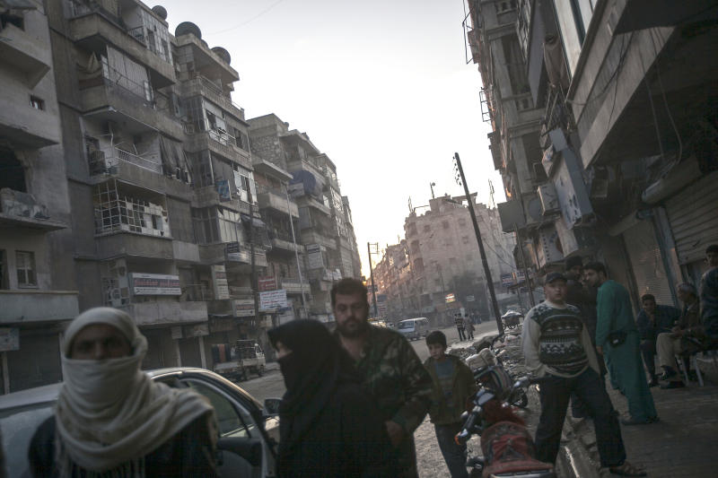 In this Tuesday, Nov. 13, 2012 photo, Syrian residents walk on a main road in the Tarik Al-Bab neighborhood of Aleppo, Syria. (AP Photo/Narciso Contreras)