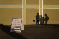 People wait outside of a polling place on Election Day, Tuesday, Nov. 3, 2020, in Las Vegas. (AP Photo/John Locher)