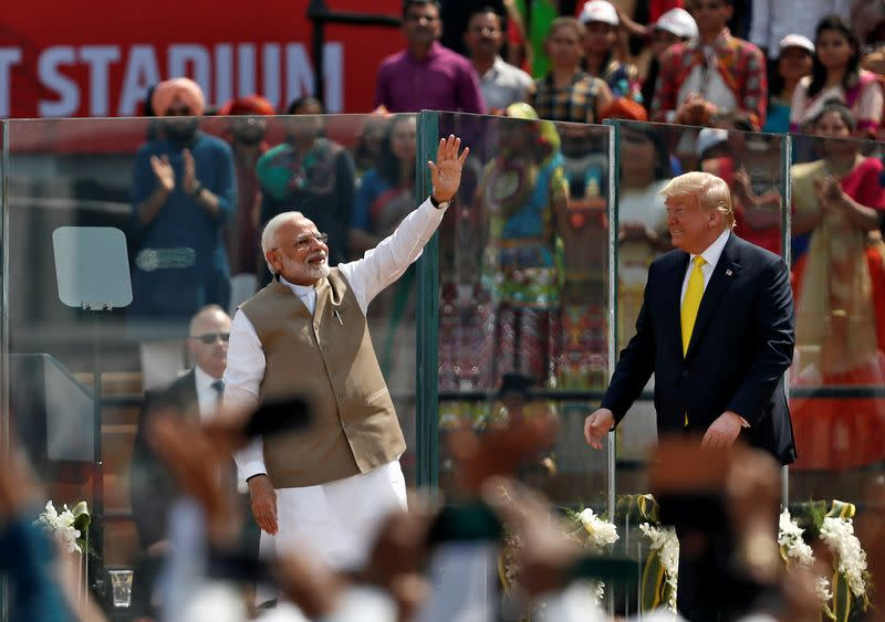 "India's Prime Minister Narendra Modi waves next to U.S. President Donald Trump as they attend the ""Namaste Trump"" event at Sardar Patel Gujarat Stadium, in Ahmedabad"