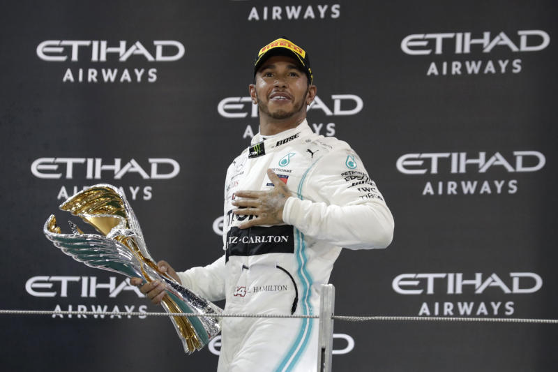 Mercedes driver Lewis Hamilton of Britain celebrates on the podium after winning the Emirates Formula One Grand Prix at the Yas Marina racetrack in Abu Dhabi, United Arab Emirates, Sunday, Dec.1, 2019. (AP Photo/Hassan Ammar)