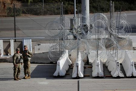 U.S. Army MPs stand by concertina wire and barricades at the U.S. Mexico border as they prepare for the arrival of a caravan of migrants at the San Ysidro border crossing in San Diego, California, U.S., November 13, 2018.   REUTERS/Mike Blake