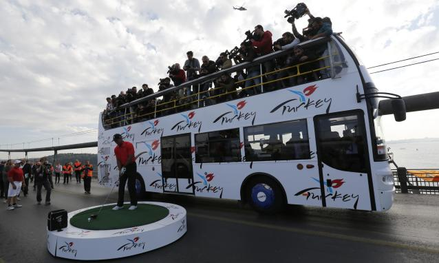 U.S. golfer Tiger Woods is surrounded by media members as he gets ready to hit a shot during an event to promote the upcoming Turkish Airlines Open golf tournament, on the Bosphorus Bridge that links the city's European and Asian sides, in Istanbul November 5, 2013. Woods is in Turkey to attend the tournament, which will take place in Antalya, southern Turkey, between November 7 to 10. REUTERS/Murad Sezer (TURKEY - Tags: SPORT GOLF)
