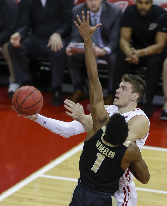 Wisconsin's Ethan Happ (22) drives to the basket against Purdue's Aaron Wheeler (1) during the first half of an NCAA college basketball game Friday, Jan. 11, 2019, in Madison, Wis. (AP Photo/Andy Manis)