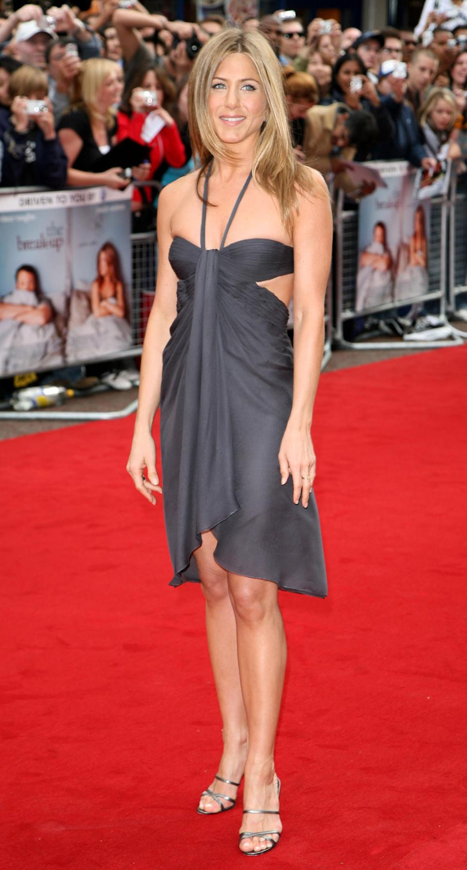 """Aniston opted for a halter gown with cut-outs for London premiere of """"The Break-Up"""" in 2006. (Photo by Tim Whitby/WireImage)"""