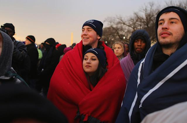 Brandon Adamski and Alicia Burke keep warm in a blanket as they and others gather near the U.S. Capitol building on the National Mall for the Inauguration ceremony on January 21, 2013 in Washington, DC. U.S. President Barack Obama, will be ceremonially sworn in for his second term today. (Photo by Joe Raedle/Getty Images)