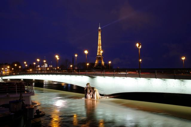 <p>An illuminated Eiffel Tower is seen next to the Seine River, with water levels raised to the height of the Zouave statue of the Pont d'Alma bridge in Paris on Jan. 25, 2018. (Photo: Geoffroy Van Der Hasselt/AFP/Getty Images) </p>