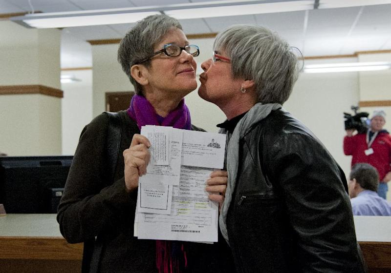 Laurie Johnson and Margaret Witt celebrate attaining their marriage license on Thursday, Dec. 6, 2012, at the Spokane County Courthouse in Spokane, Wash. Washington state now joins several other states that allow gay and lesbian couples to wed. Gov. Chris Gregoire signed a voter-approved law legalizing gay marriage. Because the state has a three-day waiting period, the earliest that weddings can take place is Sunday. (AP Photo/The Spokesman-Review, Dan Pelle) COEUR D'ALENE PRESS OUT