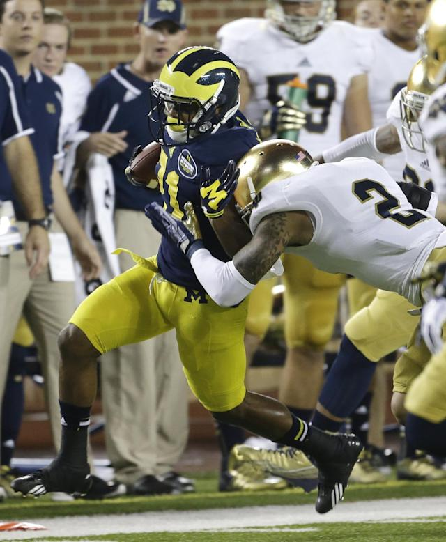 Michigan wide receiver Jeremy Gallon (21) is stopped by Notre Dame cornerback Bennett Jackson (2) during the first quarter of an NCAA college football game in Ann Arbor, Mich., Saturday, Sept. 7, 2013. (AP Photo/Carlos Osorio)