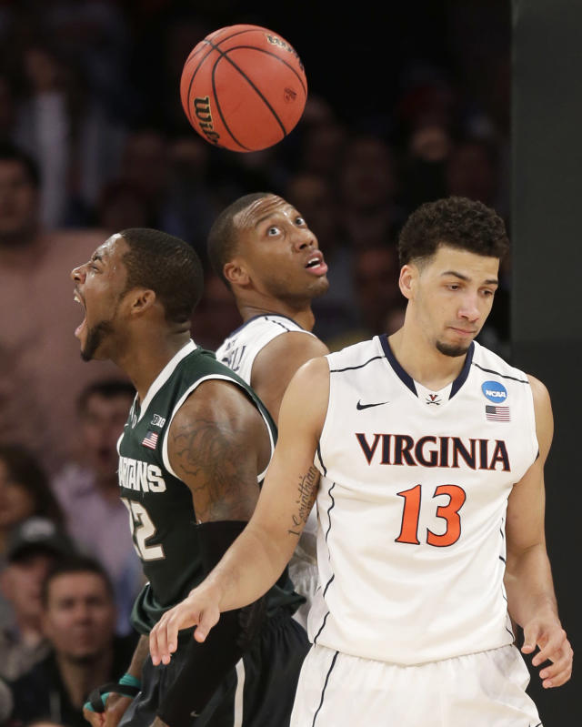 Michigan State's Branden Dawson, left, reacts after scoring, next to Virginia's Akil Mitchell, center, and Anthony Gill during the second half of a regional semifinal at the NCAA men's college basketball tournament, Friday, March 28, 2014, in New York. (AP Photo/Seth Wenig)