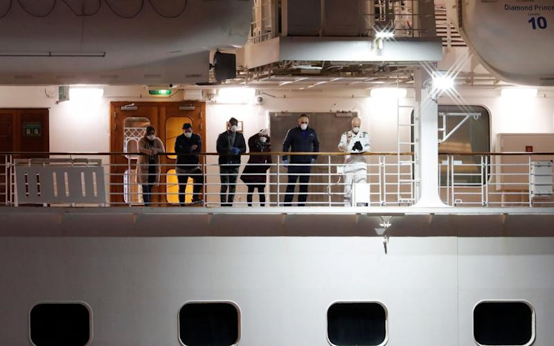 Passengers on the deck of the Diamond Princess wave to other passengers, believed to be British citizens, as they leave the coronavirus-hit cruise ship Diamond Princess - Reuters