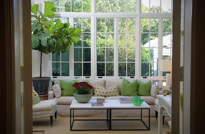 The Solarium in the vice president's official residence. A white sectional decorated with green pillows set under large windows.