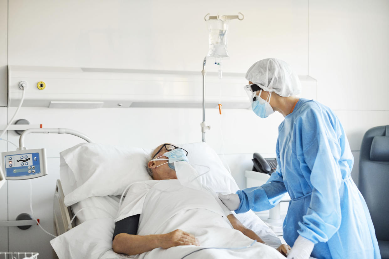 Female doctor in protective suit consoling senior patient. Elderly man with oxygen mask is lying on bed in intensive care unit during COVID-19 crisis. They are in hospital ward.
