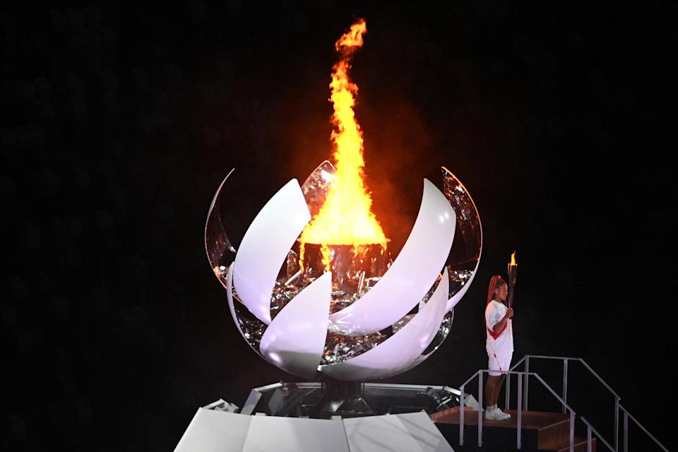 <p>Japan's tennis player Naomi Osaka holds the Olympic torch after lighting the Olympic flame in the Olympic Stadium during the opening ceremony of the Tokyo 2020 Olympic Games, in Tokyo, on July 23, 2021. (Photo by Martin BUREAU / AFP) (Photo by MARTIN BUREAU/AFP via Getty Images)</p>