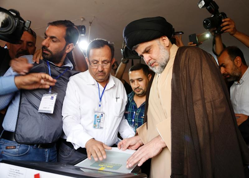 Iraqi Shiite cleric and leader Moqtada al-Sadr (C-R) casts his ballot in the central holy city of Najaf on May 12, 2018 as the country votes in the first parliamentary election since declaring victory over the Islamic State (IS) group (AFP Photo/Haidar HAMDANI)