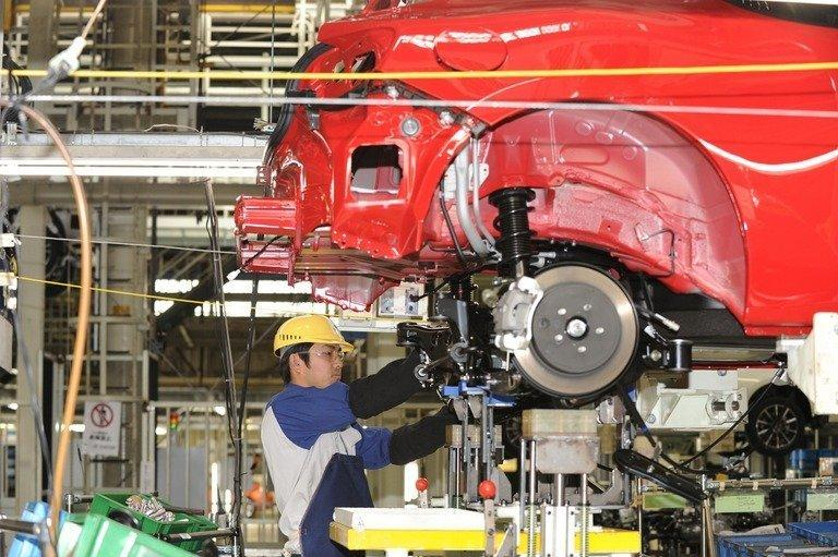 A Fuji Heavy Industries worker assembles a car at Subaru's Gunma main plant in Ota-city, Japan, on March 16, 2012