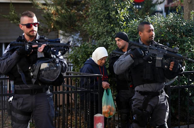 Israeli security forces stand guard as an elderly Palestinian woman walks past in Jerusalem (AFP Photo/AHMAD GHARABLI)