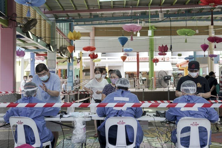 Workers in PPE register people at a table with colourful lights hanging behind.
