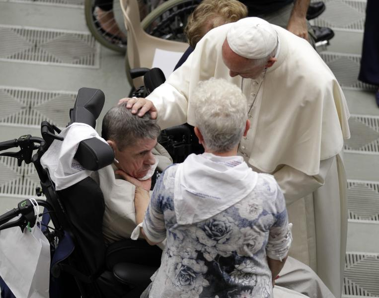 Pope Francis caresses a man during an audience with Huntington's disease sufferers and their families, in the Paul VI Hall, at the Vatican, Thursday, May 18, 2017. Francis is trying to end the stigma of people afflicted with Huntington's Disease, an incurable genetic brain disorder that causes such serious involuntary movements and psychiatric problems that sufferers are often shunned and isolated. (AP Photo/Andrew Medichini)