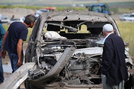 People look at a damaged car at the site of last night's explosion near the Kurdish-dominated southeastern city of Diyarbakir, Turkey May 13, 2016. REUTERS/Sertac Kayar