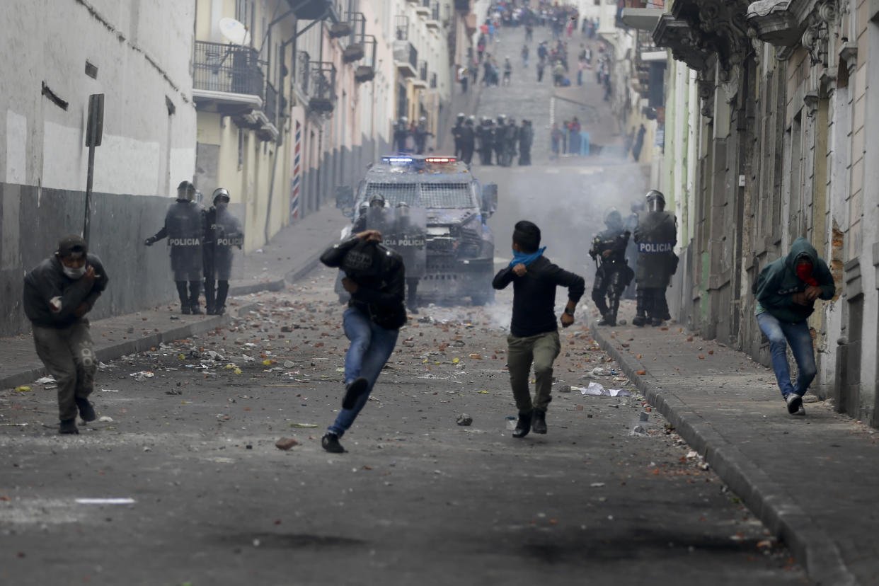 Protesters run from an oncoming armored vehicle and riot police during clashes in downtown Quito, Ecuador, Oct. 8, 2019. (Photo: Fernando Vergara/AP)