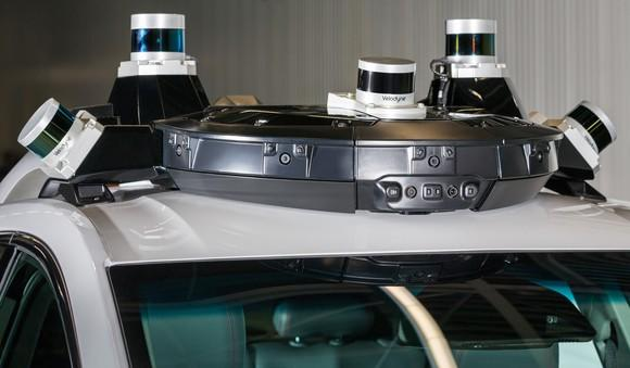 A close up of the Cruise AV's rooftop sensor array, showing several LIDAR sensors and an enclosed radar module.