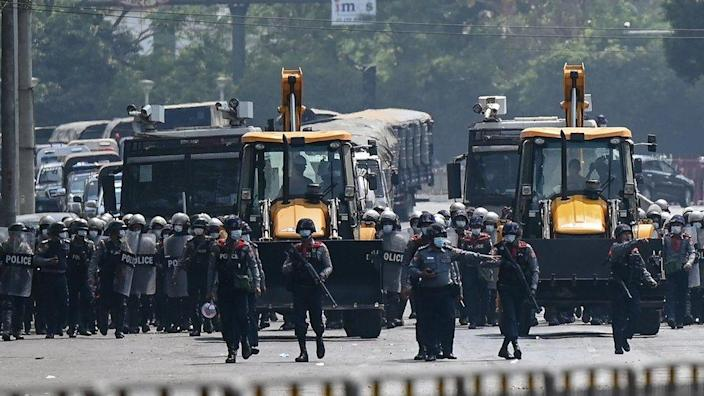 Police advance with heavy construction equipment towards protesters demonstrating against the military coup in Yangon