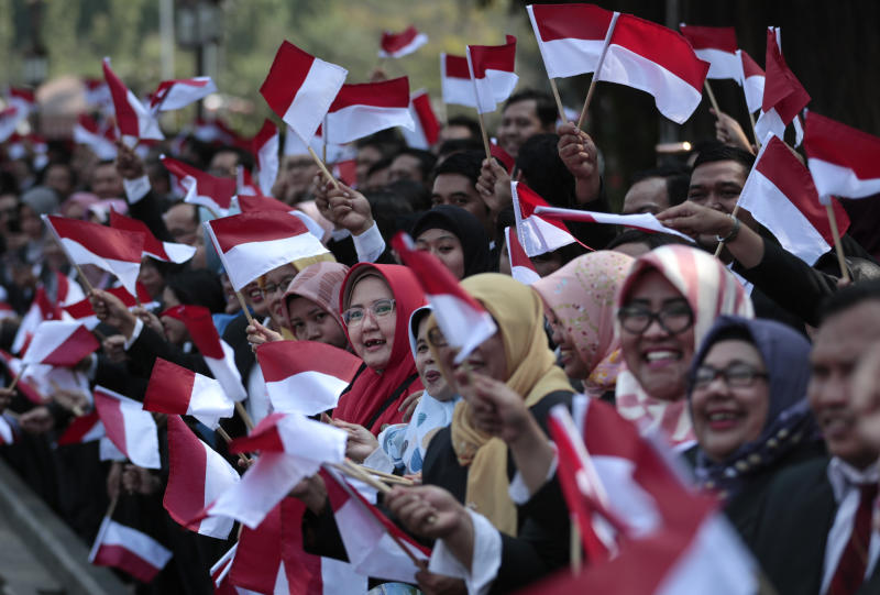 Palace staff wave Indonesian flags as the motorcade carrying President Joko Widodo leaves Merdeka Palace for the parliament building for his inauguration ceremony in Jakarta, Indonesia, Sunday, Oct. 20, 2019. The country's popular president who rose from poverty and pledged to champion democracy, fight entrenched corruption and modernize the world's most populous Muslim-majority nation is to be sworn in for his final five-year term with a pledge to take bolder actions. (AP Photo/Dita Alangkara)