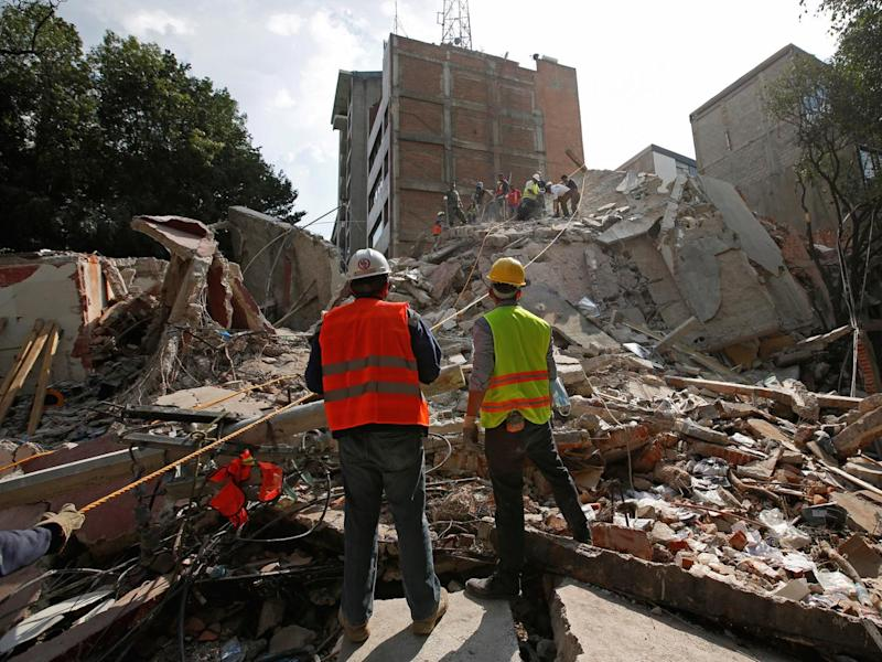 Rescue workers search for people under the rubble of a collapsed building after an earthquake hit Mexico City (Reuters)